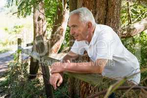 Smiling senior man leaning on wooden fence