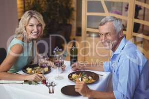 Portrait of mature couple having dinner and red wine