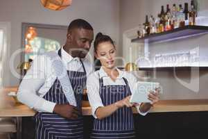Waiter and waitress discussing over digital tablet