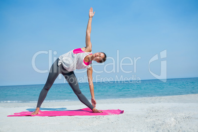 Full length of woman exercising on mat at beach