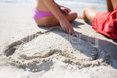 Mid section of couple sitting by heart shape carved on sand at beach
