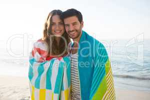 Portrait of happy young couple wrapped in blanket at beach
