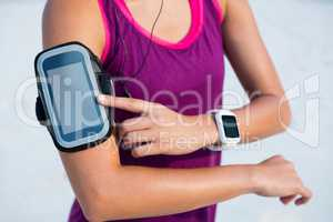 Woman wearing arm band and smart watch at beach