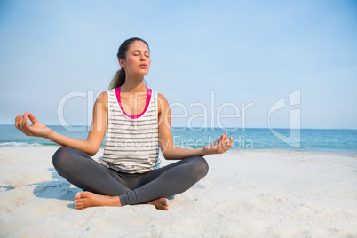 Full length of young woman with eyes closed meditating at beach