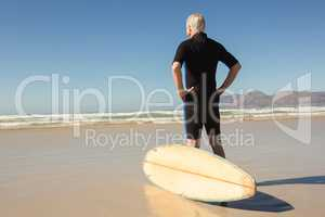 Rear view of man standing by surfboard against clear sky