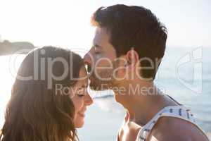 Young man kissing girlfriend forehead at beach