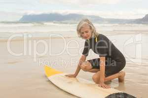Close up of senior woman preparing for surfboarding