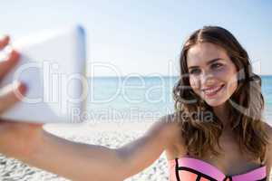 Happy young woman wearing bikini while taking selfie at beach