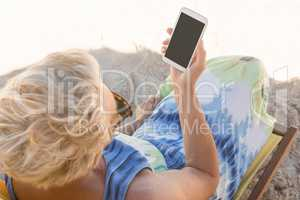 Senior woman using smart phone while sitting on chair at beach