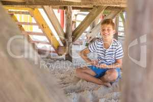 Portrait of smiling boy playing with sand while sitting under hut