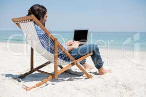 Side view of man using laptop at beach
