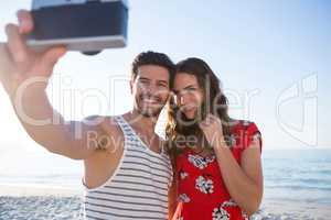 Happy young couple photographing through camera at beach
