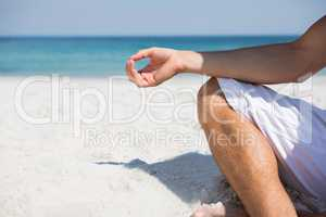 Low section of man meditating at beach