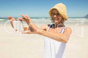 Smiling woman using smart phone while standing at beach