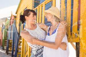 Happy mother and daughter embracing while standing against wall