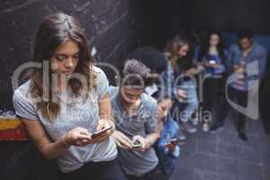Friends using mobile phones while standing by wall