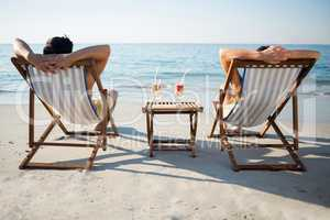 Couple relaxing on lounge chairs at beach