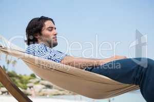 Side view of man using laptop while relaxing in hammock