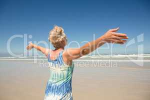 Rear view of woman with arms outstretched standing against clear sky