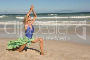 Full length of senior woman with arms raised on sand