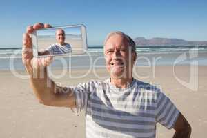 Smiling senior man holding smart phone while standing against sea