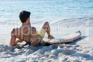 Full length of shirtless man reclining by surfboard at beach