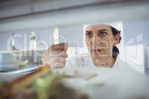 Female chef looking at an order list in the commercial kitchen