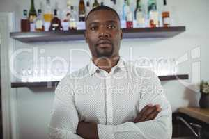 Portrait of bar tender standing with arms crossed at bar counter