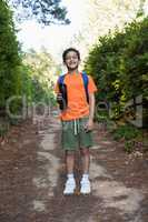 Boy with backpack and water bottle standing on the path in forest