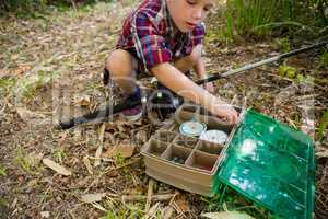 Boy with fishing rod searching in the box