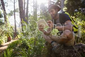 Man using digital tablet while resting on the tree stump