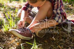 Boy tying shoelace in the forest
