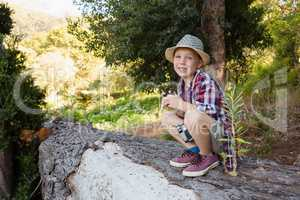 Smiling boy sitting on the tree trunk in the forest