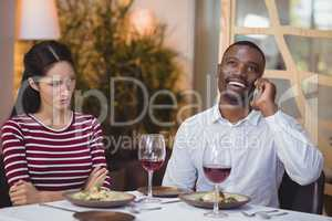 Man ignoring bored woman while talking on mobile phone