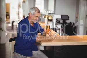 Mature man using mobile phone while having beer