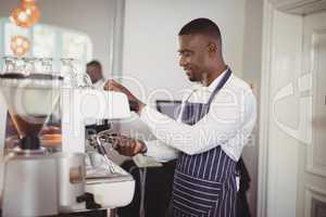 Waiter preparing espresso at restaurant