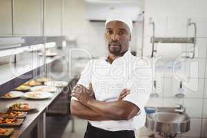 Portrait of smiling chef standing with arms crossed in commercial kitchen