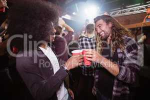 Cheerful friends toasting drinks at music concert