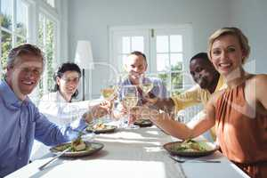 Group of happy friends toasting glasses of wine