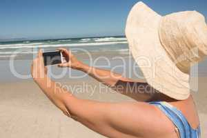 Side view of woman holding mobile phone while standing at beach