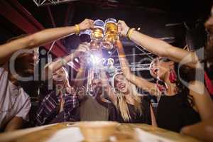 Low angle view of happy friends toasting beer glasses while sitting at table