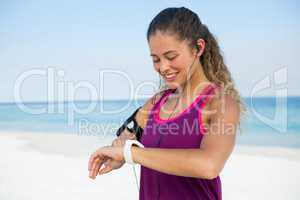 Happy woman using smart watch at beach