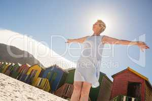 Low angle view of woman standing on sand against clear sky