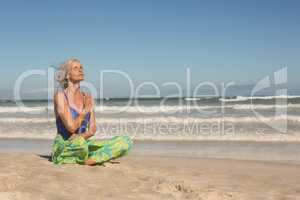 Senior woman meditating while sitting on shore against clear sky