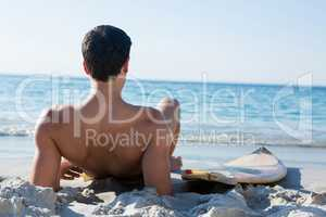 Rear view of shirtless man reclining by surfboard at beach