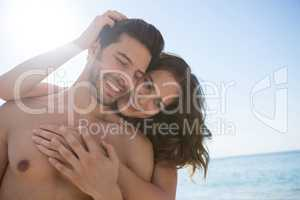 Smiling young couple embracing at beach