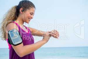 Smiling young woman using smart watch at beach