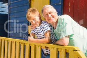 Portrait of happy grandfather and grandson leaning on railing