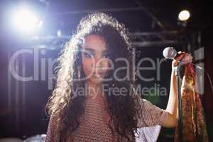Portrait of young singer holding mic at nightclub