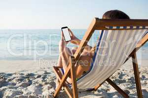 Woman using mobile phone while relaxing on lounge chair at beach